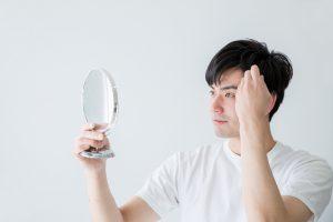 髪の毛を触りながら鏡を見ている男性の画像