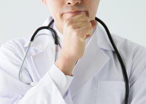 医師が顎に手を当てて考え事をしている画像