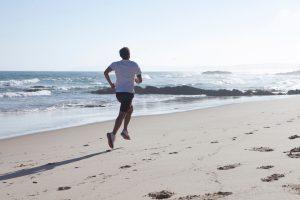 海辺を走る男性の後ろ姿