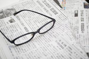 新聞の上にメガネが置いてある画像