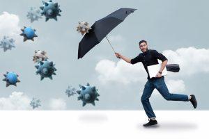傘を盾にして菌から身を守る男性の画像