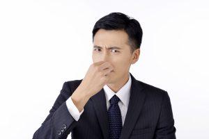 鼻をつまんで臭いを気にしている男性の画像