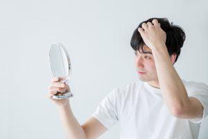男性が髪の毛を気にして鏡を見ている